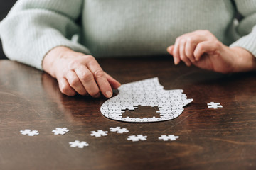 Wall Mural - cropped view of senior woman playing with puzzles on table
