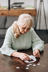 Wall Mural - senior woman with blonde hair playing with puzzles on table