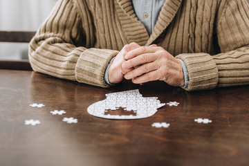 cropped view of retired man playing with puzzles on table Wall mural