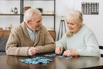 Wall Mural - happy retired couple playing with puzzles at home