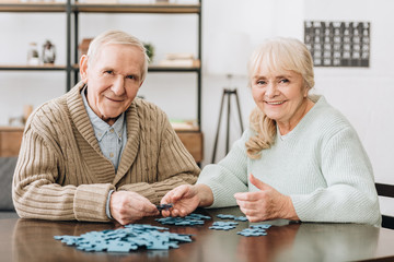 Wall Mural - cheerful retired couple playing with puzzles at home