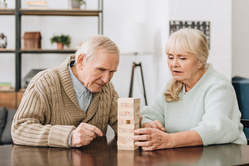 Wall Mural - senior couple playing with wooden blocks at home