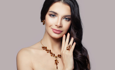 Woman jewelry. Smiling brunette woman with amber necklace, ring and earrings