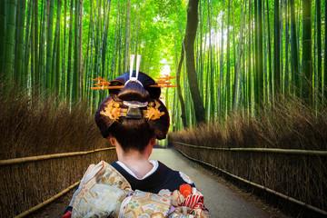 Foto op Plexiglas Asia land Woman in traditional kimono walking at bamboo forest of Arashiyama, Japan