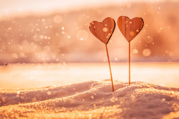 Two handmade wooden hearts in snow during warm colorful winter sunset - wallpaper or postcard for valentine - with space for your montage