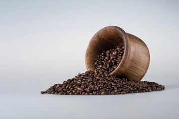 Beautiful wooden bowl on a gray background. Coffee beans are poured from the container