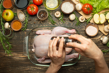 Cooking fresh chicken for a festive dinner, the hands of the chef salt and pepper the chicken concept recipe book, menu, restaurant business. Background, top view, Flat-lay