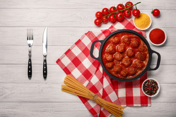 Meatballs in tomato sauce with spices in a frying pan on a white wooden board