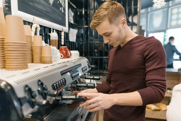 Portrait of young male barista making drinks. Coffee shop business concept