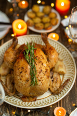 Festive baked chicken with rosemary on a festive table by candlelight