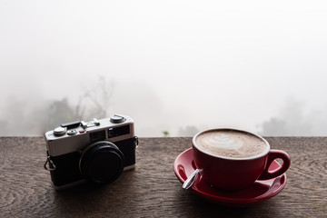 Latte art coffee and film camera on wooden table with fog view