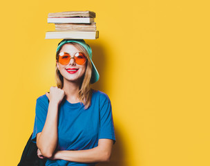 Young style student girl with orange glasses and books on yellow background. Clothes in 1980s style