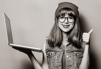 Portrait of young style hipster girl with laptop computer . Image in black and white color style