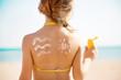child on the beach smears sunscreen. Selective focus.