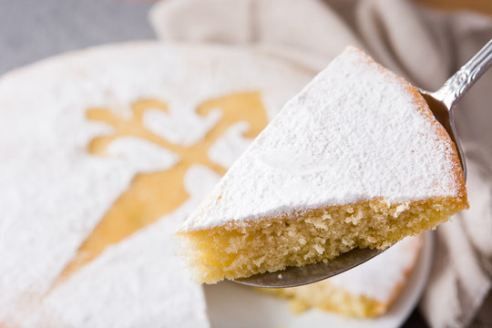 Tarta de Santiago. Traditional almond cake slice from Santiago in Spain on gray background. Close up
