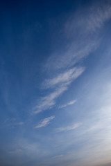 Blue sky with light cloud pattern at sunset vertical composition
