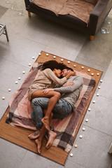 Multiethnic couple kissing on floor