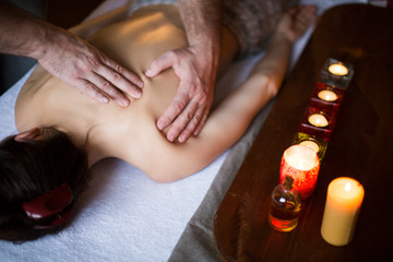 Male hands massaging female back. candles on background. Healthcare and relax concept