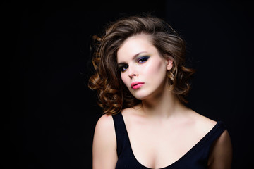 Makeup idea for elegant outfit. Attractive elegant lady with smoky eyes makeup and pink lipstick. Professional makeup. Beauty salon concept. Woman with curly hairstyle and makeup on black background