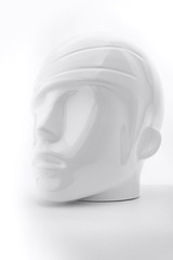 White plastic human head from mannequin as soft object with shadows, shades of gray, mild style concept
