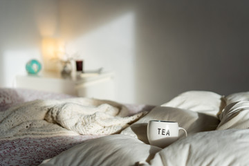 Cup of tea standing on bed