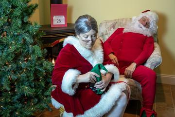 Mrs. Claus massaging Santa's tired feet
