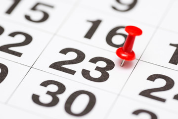 Pin on the date number 23. The twenty third day of the month is marked with a red thumbtack. Pin on calendar
