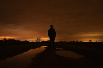 silhouette of man at sunset on dirt path between puddles reflecting the sky