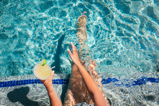 A woman waves her hand across the water while drinking a cocktail in a luxurious pool