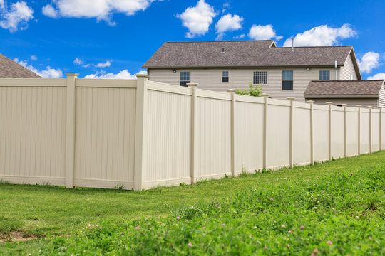 Tan colored vinyl fence surrounding a homes backyard. Grass and blue sky in the background.