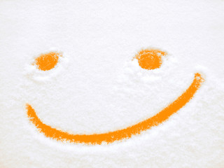 Smiley, funny orange emoticon, positive emotions, smile on snow