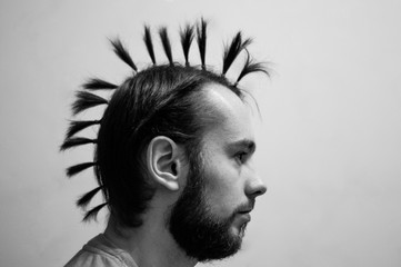 a man with a mohawk tails in profile. black and white photography