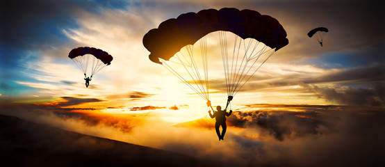 Silhouette parachutist landing at sunset