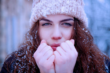 Beautiful young woman breathing on her hands to keep them warm at cold winter day.