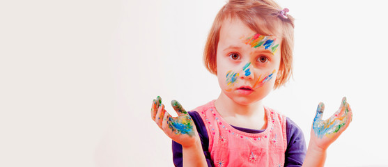 Portrait of little cute girl with children's makeup and painting colorful hands.
