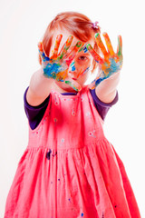 Art, creative and happiness childhood concept. Colorful painted hands and face in a cute little child girl.