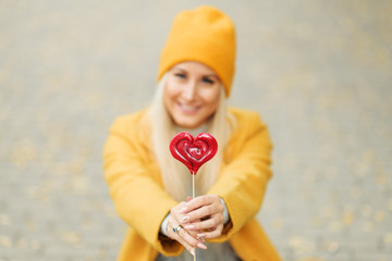 Saint Valentine's day concept. Fashion portrait blond young woman in yellow coat having fun with red lollipop heart over street background.
