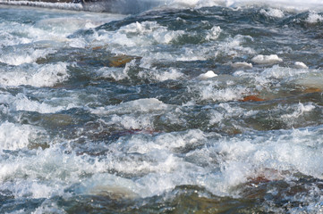 A detailed look at the water runs under the ice in the river. Snow melts from the mountains and flows in the creek