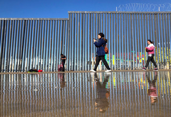 People are seen next to a section of the wall separating Mexico and the United States, at Playas Tijuana, in Tijuana
