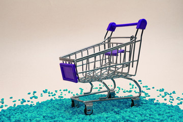one miniature shopping cart on ornamental pebbles