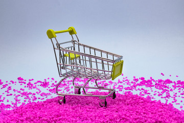one miniature shopping cart on ornamental pebbles
