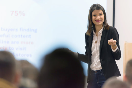 Pretty young businesswoman, teacher or mentor coach speaking to young students in audience at training seminar, female business leader speaker talking at meeting.