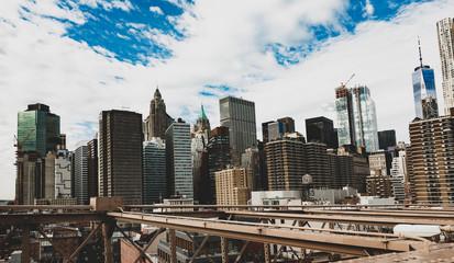 Manhattan skyline seen from the beautiful Brooklyn bridge. Cloudy day in New York City, USA.