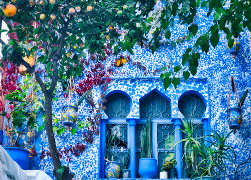 Arab style windows decorated with pots and a tangerine tree. Image taken in Chefchaouen, a beautiful village in northern Morocco