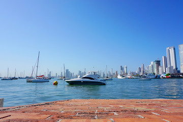 Cartagena / Colombia - 12 25 2018: Panoramic view of the coastline of the city and the sea with blue sky with some boats or ships with a sunset and buildings