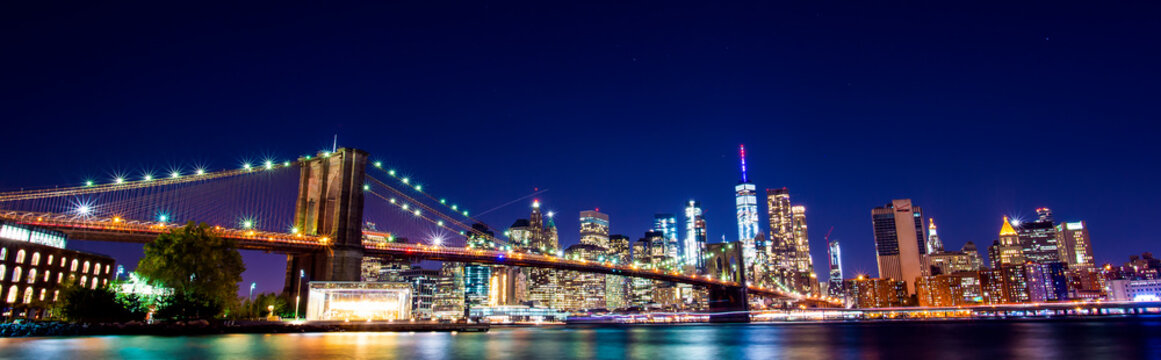 Beautiful Brooklyn Bridge and the illuminated Manhattan's skyline at dusk with dark blue sky and smooth water surface. Picture taken from the Brooklyn district, New York, USA.