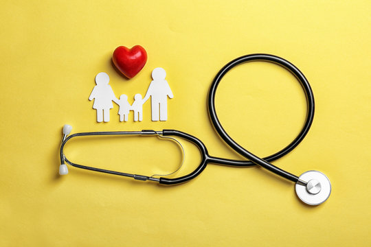 Flat lay composition with heart, stethoscope and paper silhouette of family on color background. Life insurance concept