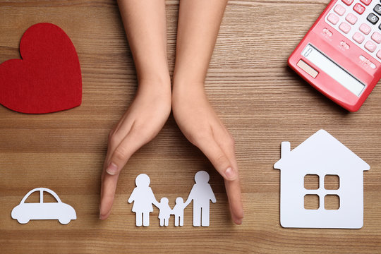 Woman holding hands over paper silhouette of family on wooden background, top view. Life insurance concept