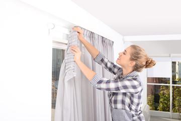 Woman hanging window curtain indoors. Interior decor element