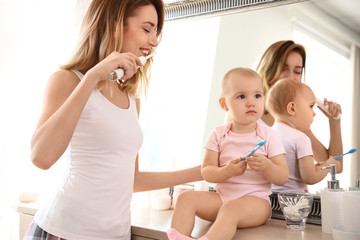 Young woman with toothbrush and daughter near mirror in bathroom
